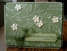 By Jessica Fick. Dry emboss design on white core cardstock. Sand to reveal white core in spots. Add cream Prima flowers & pearls in their centers. Add sentiment with ribbon.