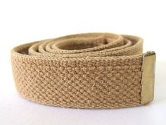 This vintage 1980s military belt is tan duck cotton webbing and one end has a brass cap. There is no buckle - a replacement for your worn out webbing!