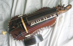 THE HURDY GURDY is a stringed musical instrument that produces sound by a crank-turned rosined wheel rubbing against the strings. The wheel functions much like a violin bow & single notes played on the instrmnt sound similar to a violin. Melodies are played on a keyboard that presses tangents (small wedges, typically made of wood) against 1 / more of the strings to change their pitch. Like most other acoustic stringed instrumnts, it has a sound board to make the vibration of the strings…