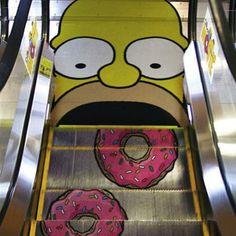 """Für die Promotion des Simpsons Kinofilms wurden Rolltreppen in diversen Einkaufszentren """"verschönert"""". Diese Ambient Marketing Simpsons Aktion ist ein super Beispiel für"""