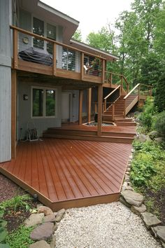 This outdoor living area has 4 levels with a cable rail railing to maximize this waterfront property. Upper ground level has a built in bench with planter box while the lower ground level deck has a beautiful Japanese style water feature. Two Level Deck, Ground Level Deck, Multi Level Decks, Patio Deck Designs, Patio Design, Terrace Design, House Design, Tiered Deck, Deck Stairs