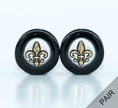 """Pair of Handmade Gold and Black Fleur De Lis Plugs - 0g, 00g, 1/2, 9/16, and 5/8 inch. A pair of handmade see through Fleur De Lis plugs, featuring a gold fleur de lis """"floating"""" in a black acrylic plug. A silver fleur de lis can be requested. The Fleur De Lis has many meanings but my personal favorite is loyalty. Also, perfect for any New Orleans or Saints fans! These plugs are very lightweight and comfortable as well as easy to put in as they have a screw off backing. Available in 0g…"""