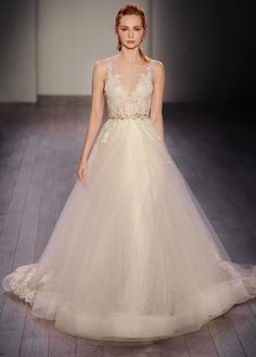 Champagne tulle bridal ball gown, ivory/gold alencon lace shear appliquéd bodice, metallic leaf trim at natural waist, circular tulle skirt accented with lace appliques, hemline finished with horsehair, chapel train. Also available in Ivory/Silver.