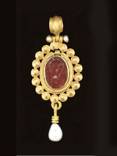 A ROMAN GOLD AND CARNELIAN PENDANT   Circa 1st Century A.D.   The flat oval stone deeply engraved with a facing bust of Minerva, her head turned slightly to her right, wearing a cuirass and a triple-crested Attic helmet, bezel set, the backing with a projecting flange rolled into a suspension loop above; the entire pendant now fitted into a larger modern pendant fringed by a band of disks and supporting a pearl drop