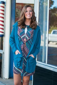 """This teal cardigan is a fall fashion dream! From the color to the cozy material, this flawless fitting beauty is just what you need! It brightens up any outfit and just look at how amazing that hood is!   Material has generous amount of stretch. Pockets and a hood.  Sara is wearing the small.   Length from shoulder to hem: S- 33""""; M- 34""""; L- 35""""."""