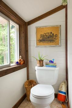 Mosaic tile, painted tongue-and-groove paneling, and barn-wood trim finish this commode area.