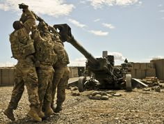 TEAMWORK -- Members of 3rd Platoon, Alpha Battery, 1st Battalion, 77th Field Artillery Regiment, 172nd Infantry Brigade, work at dislodging their M-777 155mm howitzer from the three-foot deep hole it dug its spades into after firing several rocket-assisted projectiles, Sept. 4. The huge weapon weighs 9,000 pounds and can launch projectiles over 30 kilometers. Photo by Spc. Ken Scar