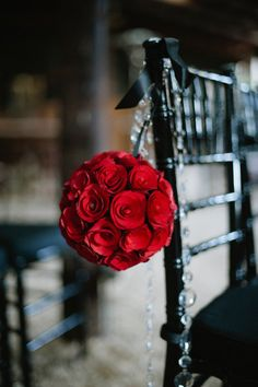 aisle decor - ball of red roses with black chairs. Cute!