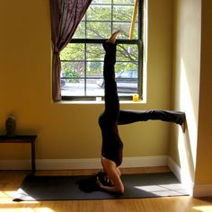 One-Legged Bound Headstand Against a Wall: From Bound Headstand Against a wall, slowly lift one leg into the air, keeping the other foot pressing against the wall. Be careful not to lift your leg past your head or you might lose your balance. Hold here for five breaths, lower your top leg, and then switch.