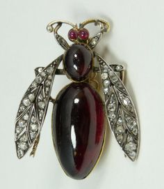 "18k yellow gold pin mounted with ruby jewels to body and diamonds wings. Holds large oval cabochon ruby approx. 28mm x 14.8mm x 9mm set as abdomen. Holds another oval cabochon ruby set as thorax 10.6mm x 7.1mm x 6mm. Also has two small round cabochon rubies set to eyes. Wings and legs adorned with round cut white diamonds approx. 2ctw. Measures Total weight of 1 3/4"" length x 1 3/8"" width (4.4cm x 3.4cm). Total weight of 10.4dwt / 16.3 grams."