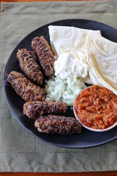 Cevapi - Kebab made out of grilled minced meat or pork, beef and or lamb served in with a flat bread with chopped onions, sour cream and ajvar (red bell pepper relish)
