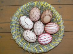 A bowl of eggshells with decorative wiring.