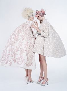 From left: Birley wears Giambattista Valli Haute Couture coat and shoes; Ashley Lloyd headpiece. Delevingne wears Giambattista Valli Haute Couture dress and shoes; Luigi Scialanga for Giambattista Valli Haute Couture necklace. Beauty note: Perfect every inch of leg with Valmont Body Time Control Cellular Refining Scrub. Hair by Malcolm Edwards at Streeters London; makeup by Val Garland at Streeters London; manicures by Trish Lomax at Premier Hair and Make-up. Produced by And Productions…