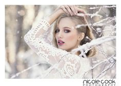 senior portrait posing idea for girls - arms raised to form triangles and frame the model's face. Winter snow shoot with frosty branches in the foreground and soft snow falling. Monochromatic tones with white textured dress with floral embroidery, and pink eyeshadow, rosy cheeks and pink lipstick.