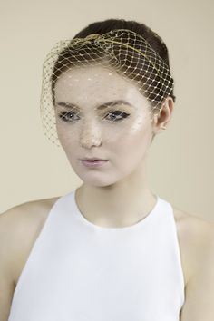 Our Dita birdcage veil, made in gold colour veiling is finished with gold  sequins and attaches with a headband.  This veil can be worn as seen here or with one of our hat designs. Please  get in touch for the combined price if you are considering buying a hat and  a veil.  Made to Order.