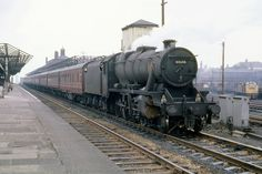 Stanier 8F 2-8-0 48646 at Wigan North Western with a train of empty condemned coaches for Edge Hill.  EE Type 4 1Co-Co1 D390 lurks in the background.  12th March 1968