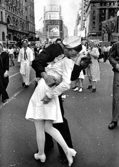 """Um beijo na Times Square (1945) - Repleta de mistérios, esta fotografia foi imortalizada pela revista """"Life"""". Uma das hipóteses é que, durante o anúncio do término da Segunda Guerra Mundial e dos ataques contra o Japão, em 14 de agosto, o fotógrafo Alfred Eisenstaedt registrou o marinheiro beijando a jovem mulher de vestido branco. O marinheiro possivelmente estava passando quando viu a enfermeira na rua e a agarrou."""
