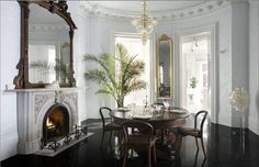 dining-room-ebony-wood-glossy-floors-capiz-lamp-glass-light-chandelier-palm-round-table-carved-stone-fireplace-pale-blue-wall-wallpaper-ornate-crown-molding