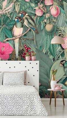 Your teen will fall in love with this bedroom interior! From monochrome spotty bedding, and a matching headboard, to pretty pink lamps and retro phones, this bedroom interior is the perfect escape for a young adult. Complete the look with a statement wall behind the bed. This tropical jungle wallpaper is rich in sage green and pink shades, super on trend for 2021 and 2022! Get the look at Wallsauce.com
