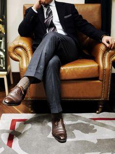 Grey pants, blue blazer, brown leather.