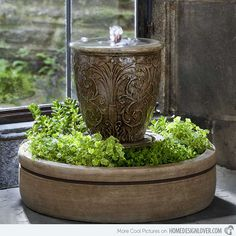 The details in this urn with fountain are very beautiful. It is even enhanced with the addition of green plants at its bottom.
