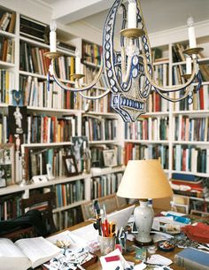 Work Space Photo - A beaded chandelier above a wooden desk surrounded by books