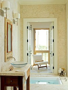A sunken Japanese soaking tub looks supremely serene. Creamy stone on the floors and walls, and a simple wood vanity topped with a glass-bowl sink contribute to the spa-like setting. (Photo: Colleen Duffley)