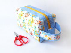 A medium-sized zippered boxy pouch made out of cotton fabrics. Since it opens wide and has lots of space, it can be used for many things. It makes a great make-up bag and can fit brushes and cosmetics. It also makes a good knitting/crochet/sewing project bag, with enough space for yarn, needles or fabric. Also makes a great storage bag for toys or baby items, or even a large pencil pouch to store crayons and markers.  Size: • 21 × 10 × 10 cm (8½ × 4 × 4) The main outer fabric featu...