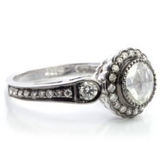 18K white gold vintage inspired ring set with a rose cut diamond in the center. The ring contains a black rhodium finish with a halo of brilliant cut diamond accents. Each ring is one of a kind, and prices may vary based on what is in-stock at the time of purchase. PRICING:Due to daily fluctuations in precious metal & gemstone costs, prices are approximate; subject to change. Prices will vary based on a clients requested specifications