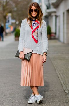 Mulher posa com look comfy usando tricot cinza, saia midi plissada, tênis branco e finaliza o look com um lenço clássico amarrado no pescoço