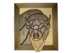 """Bison - intarsia Wood Carving by Silver Creek. $260.95. Bison-Intarsia wood carving, made by hand in Wisconsin of native grown oak. Individual pieces are cut, shaped, sanded, stained, and then glued onto a plywood backing. Natural graining of the wood makes each item unique. Measures approximately 10"""" wide x 16"""" high, and comes ready to hang on your wall. Frame style will differ from photo."""