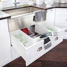 Afin de ne pas perdre d'espace, un tiroir a été inséré sous l'évier. Conçu sur mesure pour épouser la forme du drain, il permet de ranger des produits et accessoires de nettoyage grâce à des séparateurs.