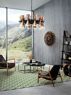 A copper suspension lighting piece catching all the attentions in a vintage design set with black lounge chairs, a modern coffee table and a patterned rug byDelightFULL