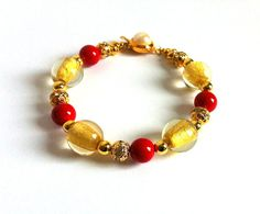 24K Gold Foil Red Jade Handmade Beaded by ClearWaterDesignsbyK Https://clearwaterdesignsbyk.etsy.com Https://clearwaterdesigns.info This gorgeous handmade beaded bracelet has glass beads with 24K Gold Foil, stunning Red Jade beads, & gold Rhinestone Filigree beads for extra glitz.   This is a beautiful bracelet for a night out. I've finished it off with an easy to wear Pearl Slide Clasp.