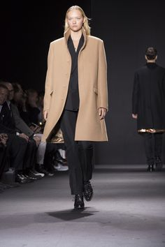 An androgynous Gemma Ward in a camel stand-up collar overcoat styled with a black suit on the Fall 2016 men's Calvin Klein Collection runway. #mfw
