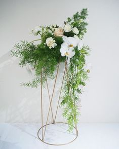 Bloodwood Botanica   Creative and unique tall floral wedding centerpiece. Made using a copper plant stand and cascading asparagus fern, white phalaenopsis orchids, roses and ranunclus