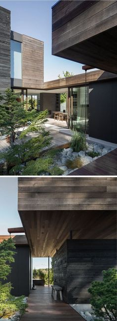 This modern house has a wooden path that leads from the sidewalk to the front door and a courtyard that's surrounded by plants.