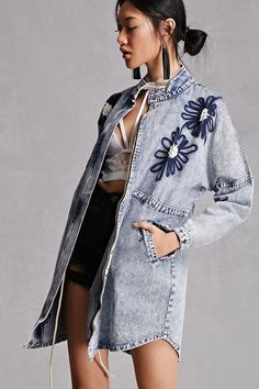 A longline mineral-wash denim jacket featuring floral embroidery with faux pearl accents, high neckline with snap-button closure, zip-up front, a drawstring waist, curved hem, two front flap snap-button pockets, and long snap-button cuff sleeves. This is an independent brand and not a Forever 21 branded item.