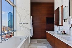 Suzie: More Design Build - Modern city bathroom cherry floating double vanity, marble counter ...