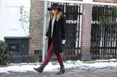 red bottom, grey sweater, black coat, blk shoes