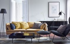 A modern living room with a yellow SÖDERHAMN sofa, VILSTAD armchair and footstool in black, and a black TOFTERYD coffee table.