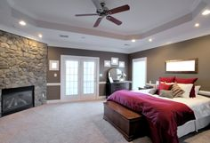 Large master bedroom with beige color scheme, rock wall with gas fireplace, French doors to the outside and tray ceiling
