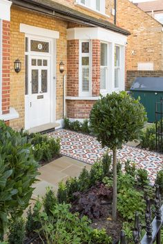 Custom London front garden design with tiled, mosaic path