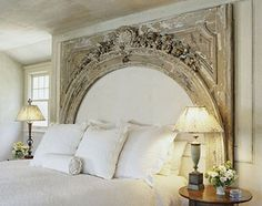 Archway headboard, almost makes the bed feel cosier and smaller. With a fireplace mantel maybe?