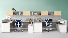 Two Action Office workstations with gray fabric wall panels, white storage units, and blue Mirra 2 ergonomic desk chairs. Herman Miller, Office Furniture, Furniture Design, Cool Office Desk, Office Workstations, Office Cubicles, Used Chairs, Ergonomic Chair, Office Interiors