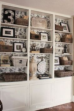 like the decorative paper at the back of the shelves ~ also like the mix of items, nice repeat of baskets, clocks, pictures & the silver tray