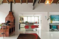 No projeto da decoradora Neza Cesar, forno e fogão a lenha ganham destaque na sala de pé-direito alto, integrada com a cozinha (ao fundo).