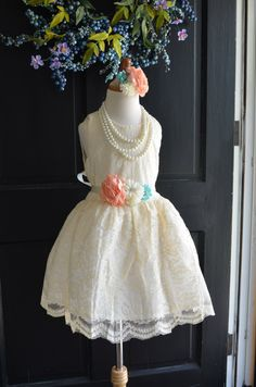 Beautiful little girls special occasion dress. Made of antique-looking ivory bridal lace, has an embellished sash that includes coral and mint chiffon flowers and this includes a matching headband. Perfect for your next special event.