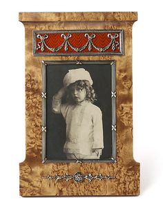 A rare Karelian birch photograph frame by Fabergé, in the form of a pediment, with a rectangular aperture in a reeded silver bezel tied with gilded red ribbons, containing an original photograph of the Tsarevitch Alexei Nikolaevitch, surmounted by a panel enameled scarlet over a moiré guillochage and applied with chased silver gilt festoons, mounted below the aperture with silver bellflower and rose motifs gilded green and red. Workmaster: Anders Nevalainen, St. Petersburg, circa 1907.