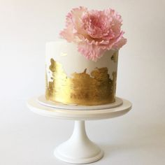 Eine traumhafte Hochzeitstorte mit Blütenschmuck und goldenem Fondant